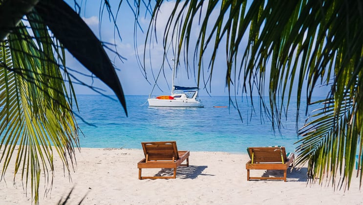 Two empty wooden chaise loungers sit on a white-sand beach with palms swaying & a private catamaran sitting offshore during the Belize Sailing Adventure charter cruise.