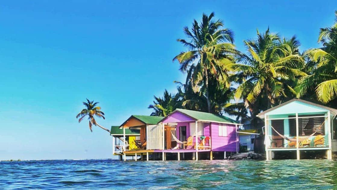 Colorful beach houses sit on stilts above clear blue waters with palm trees above, on a sunny day during the Belize Sailing Adventure charter cruise.