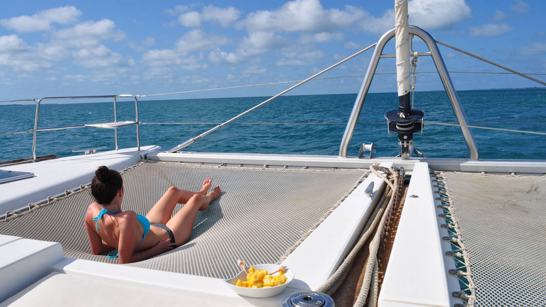 Woman in a bikini lounges on the trampoline netting at the front of her private catamaran on a sunny day in Belize during the Belize Sailing Adventure charter cruise.