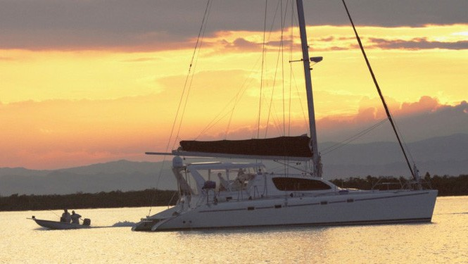 the sun is setting with a orange and yellow sku behind the Belize charter ship Palometa, an all white catamaran with the sails down