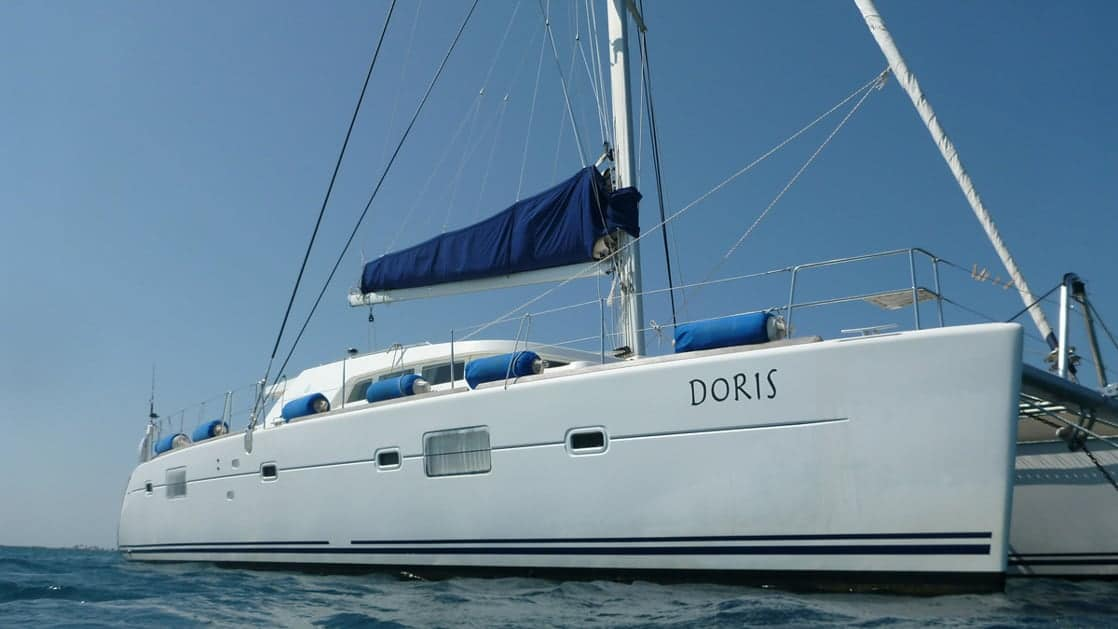 Exterior of the Belize charter ship Doris, all white with royal blue sails, she sits on the ocean on a clear blue sky day