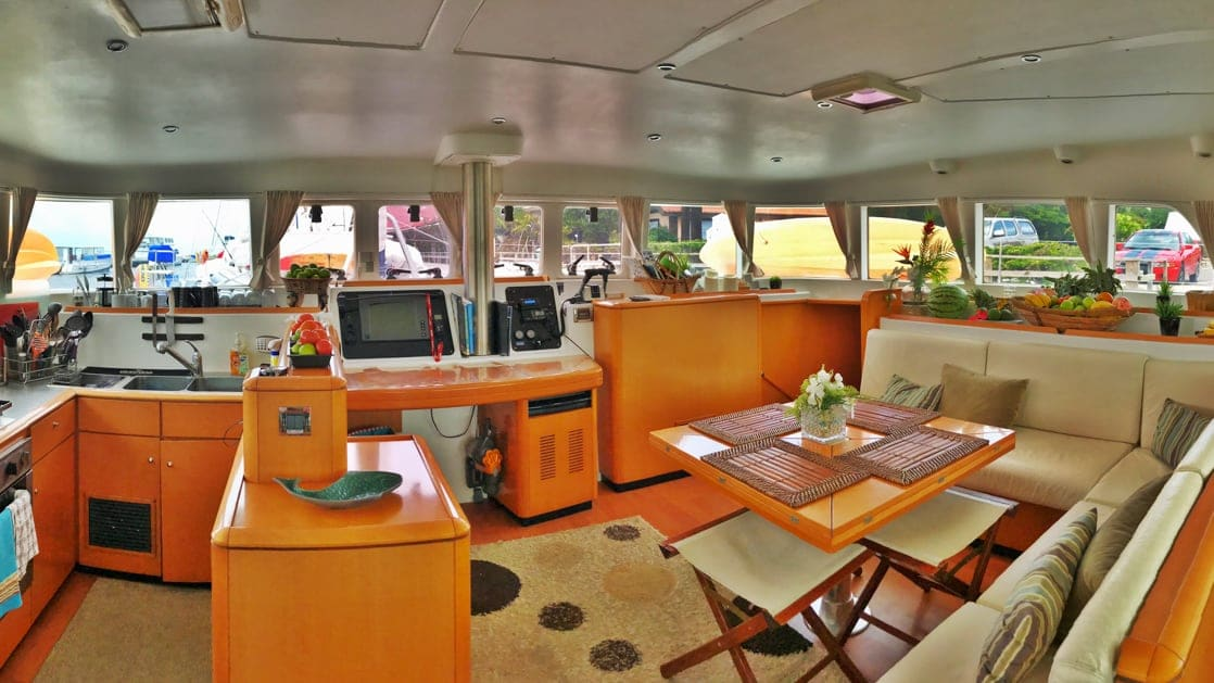 indoor Salon aboard Belize charter ship Doris, wooden furniture with upholstered seating area around a sqwuare table, 12 windows surround the room
