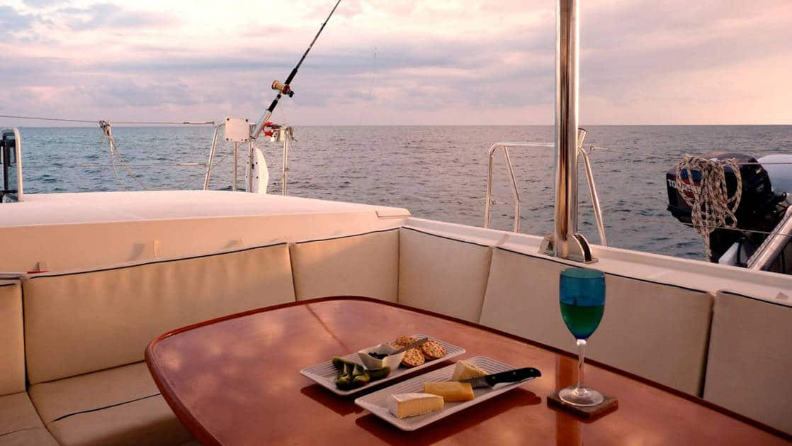 Al fresco dining aboard Belize charter ship Doris, the sun is setting over the ocean orizon, on the table are plates of appetisers and a glass of wine.