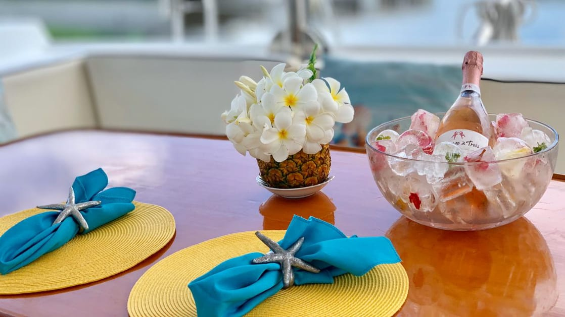 Al fresco dining table aboard Belize charter ship Island Girl, tww yellow and teal place met settings with a center piece of flowers and a bowl of ice with chilled champagne
