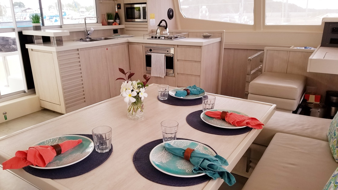 Interior Salon beige table with view back to modern, clean galley aboard Endless Options Belize catamaran.