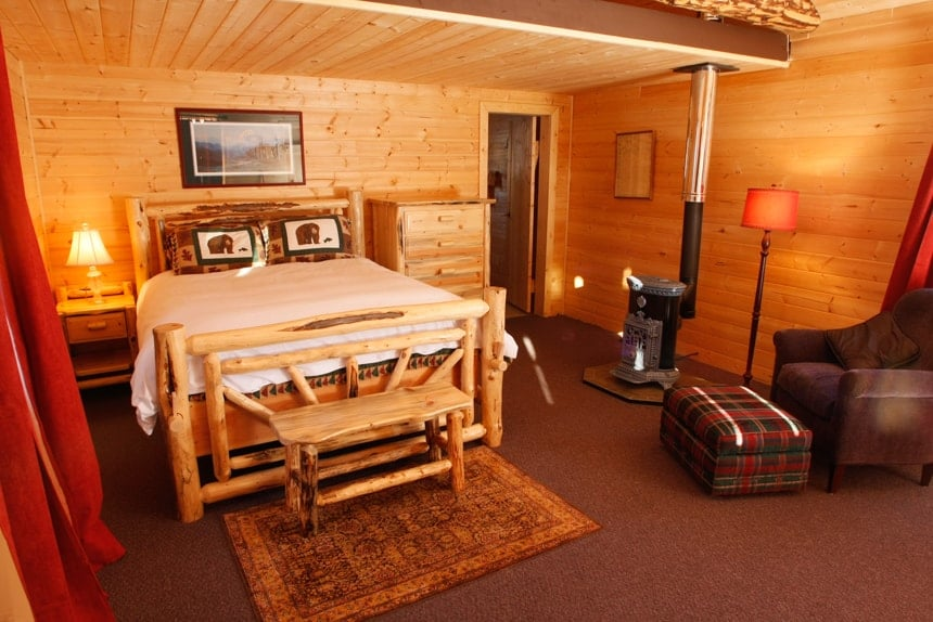 Inside the rustic cabin at Winterlake lodge, wood log walls, with a wood burning stove and a kind side bed