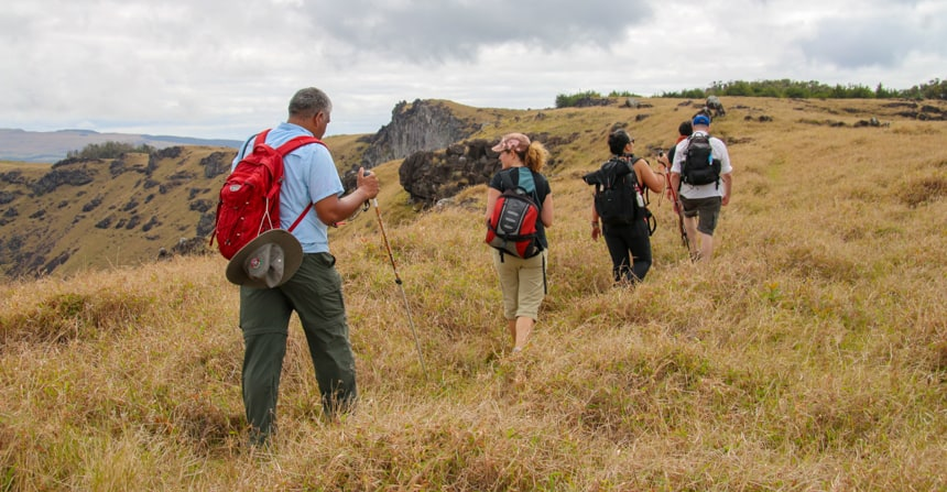 A group of travlers walk in a meadow on Easter Island while staying at Explora Rapa Nui Lodge
