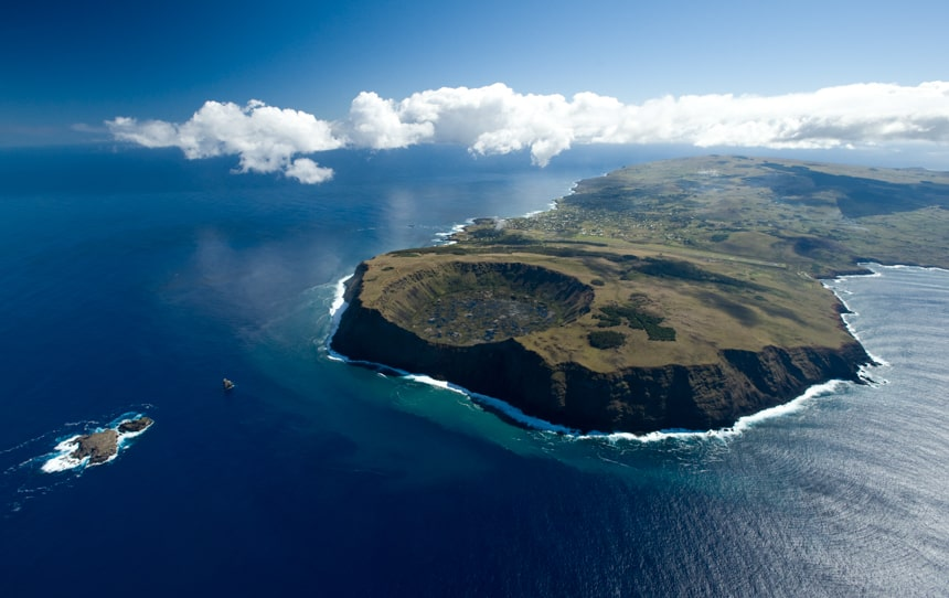 an aerial shot of Easter Island, a green land mass island that sits in the green ocean and matching blue sky