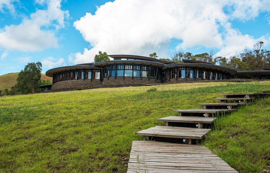 Explora Rapa Nui Lodge, a circular stone buildings with wrap around windows sit on a grassy hisiude witjh wooden steps reaching to it.