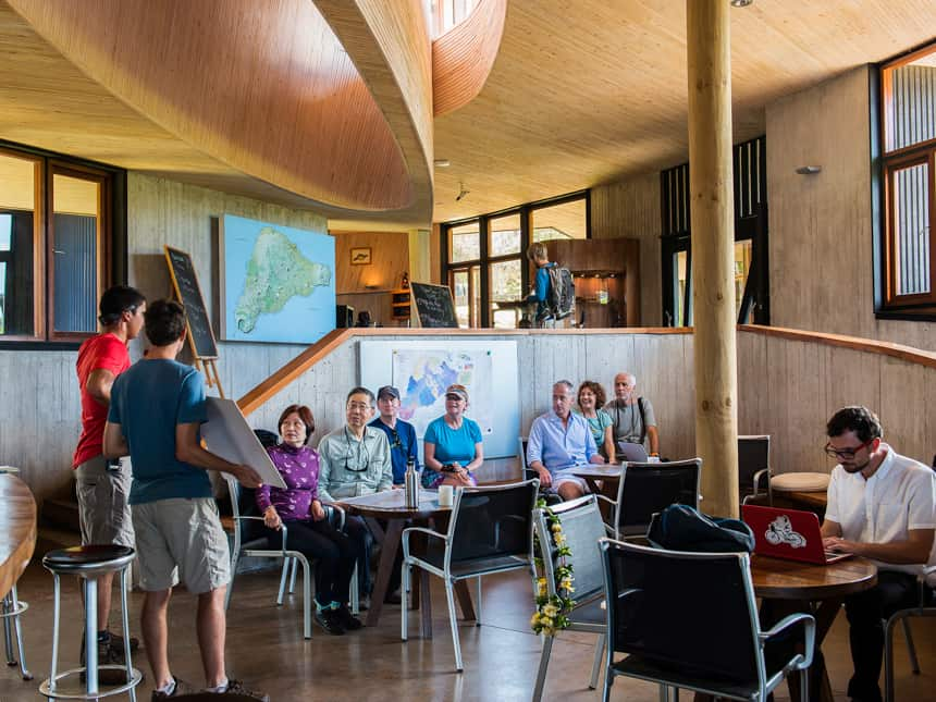 a group of travlers sit in the lounge of Explora Rapa Nui Lodge, they lsiten to their guides discuss the days activities
