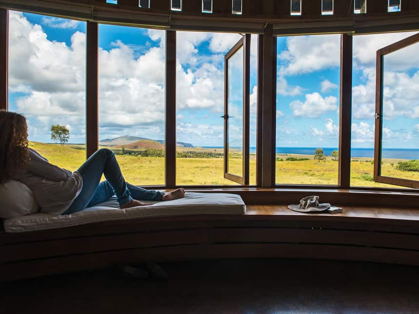 at Explora Rapa Nui Lodge, a female travelers lays on a bench seat infront of windows that open to the outside, a view of a green meadow and blue ocean in the distance