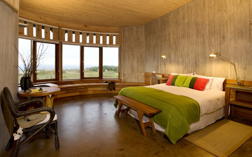 a suite inside Explora Rapa Nui Lodge, natural earth tones used throughout a circular room with tall windows and a seating area