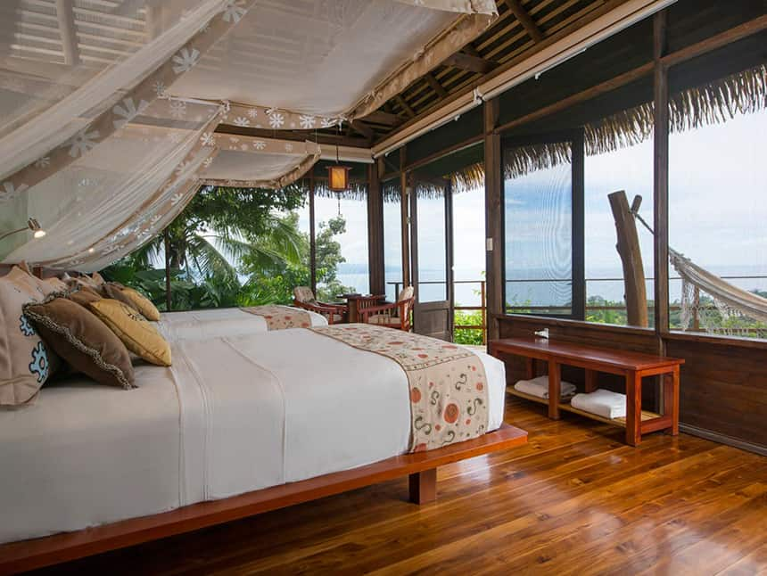 a cabana room with a king side bed and bug net, panoramic wrap around windows and a hammock at the Lapa Rios Eco Lodge Costa Rica,