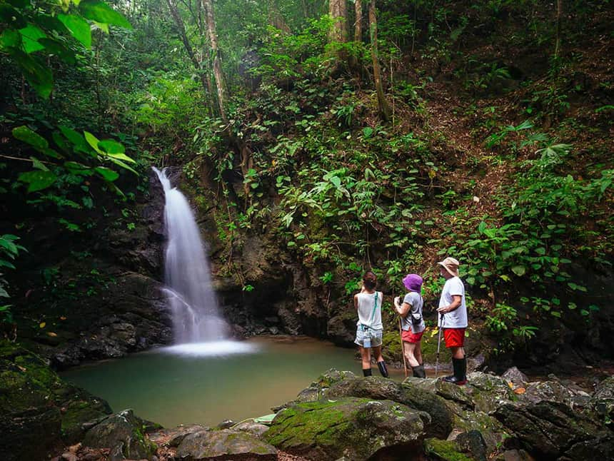 three travelers stand infront of a waterfall in the costa trican jounge at the Lapa Rios Eco Lodge