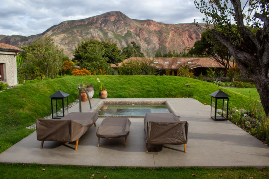 outdoor jaccuzi area at Sol Y Luyna, a Sacred Valley Peru Lodge, surrounded by grass and a jagged mountain range