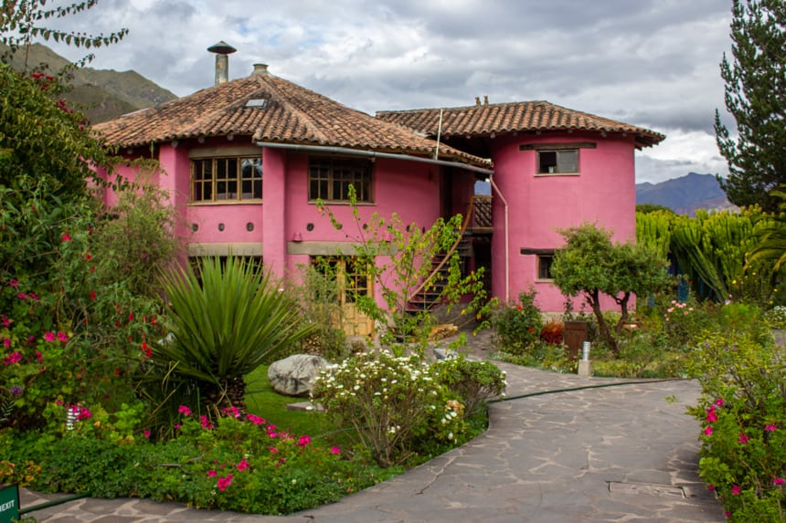 Pink clay buidling at Sol Y Luna, a lodge in Peru's Sacred valley, a stone walk way winds betwwen green grass and colorful flower beds
