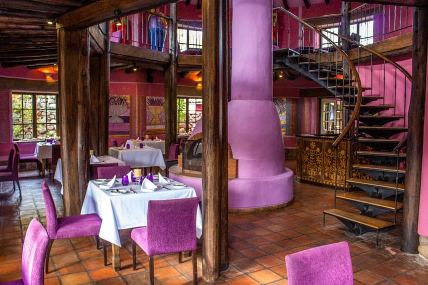 bright purple walls, chairs and fireplace decorate the inside dinning area of Sol Y Luna, a lodge in the Sacred Valley of Peru