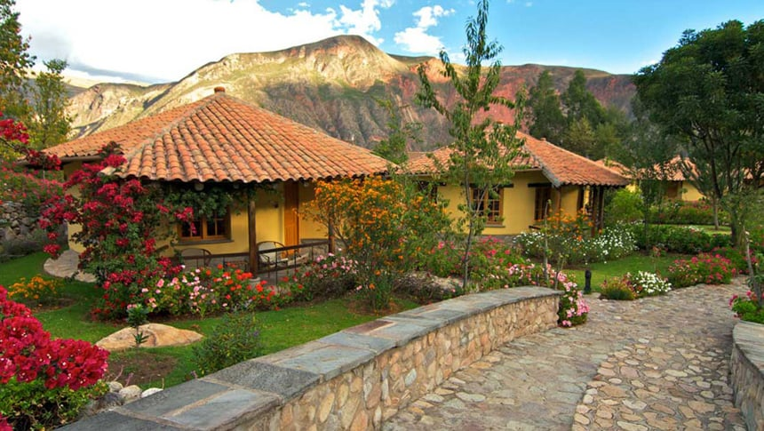 Yellow clay buidlings at Sol Y Luna, a lodge in Peru's Sacred valley, a stone walk way winds betwwen green grass and colorful flower beds