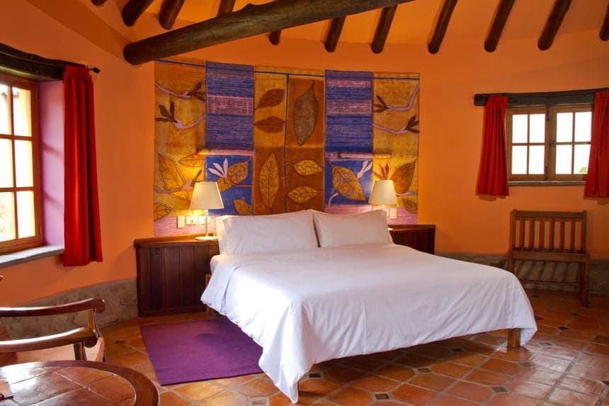 A room inside Sol Y Luna a Peru Lodge inside the Sacred Valley, orange walls with red window covers, a white queen bed sits agains peruvan wall art
