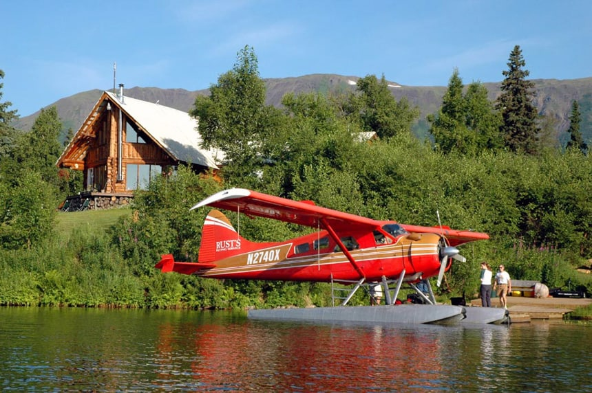 A bright red float plane sits in front of the dock at Winterlake Lodge in Alaksa behind it is lush forest with the lodge sitting ontop of the hilllside
