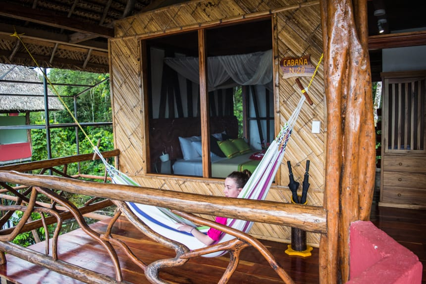 a traveler lays in a hammock on her front porch of a cabana at Napo Wildlife Center in the Ecuadorian Amazon