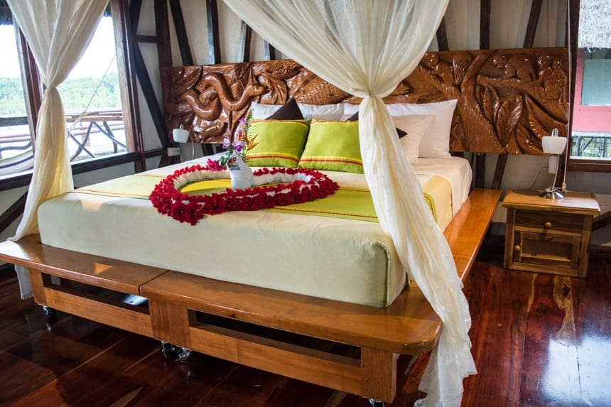 inside a cabana at the Napo Wildlife Center, a king bed with a heart made of flowers sits infront of a wodden cardev headboard surrounded by a bug net