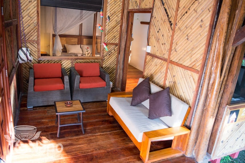 a second lounge area in a suite at the Napo Wildlife Center, two red accent chairs and a love seat sit inside a bamboo walled room.