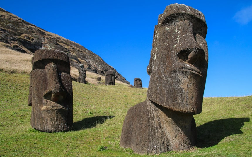 stone sculpures of faces on Easter Island sit on green hiullside ifnron of a blue sky, seen while staying at Explora Rapa Nui Lodge