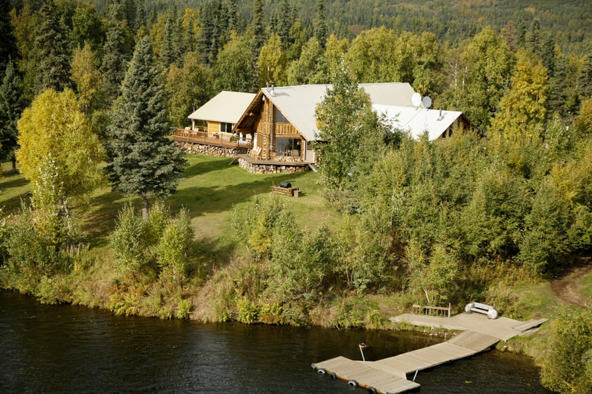 An areal view of the Winterlake Lodge, surrounded with lush green forest, with a dock on the lake