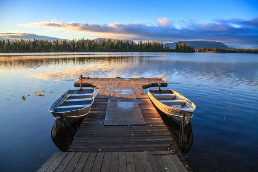 a dock floats with two metal boats tieds up to it at Winter lake Lodge in Alaska the glow of the setting sun is seen over the forest of trees on the opposite side of the lake