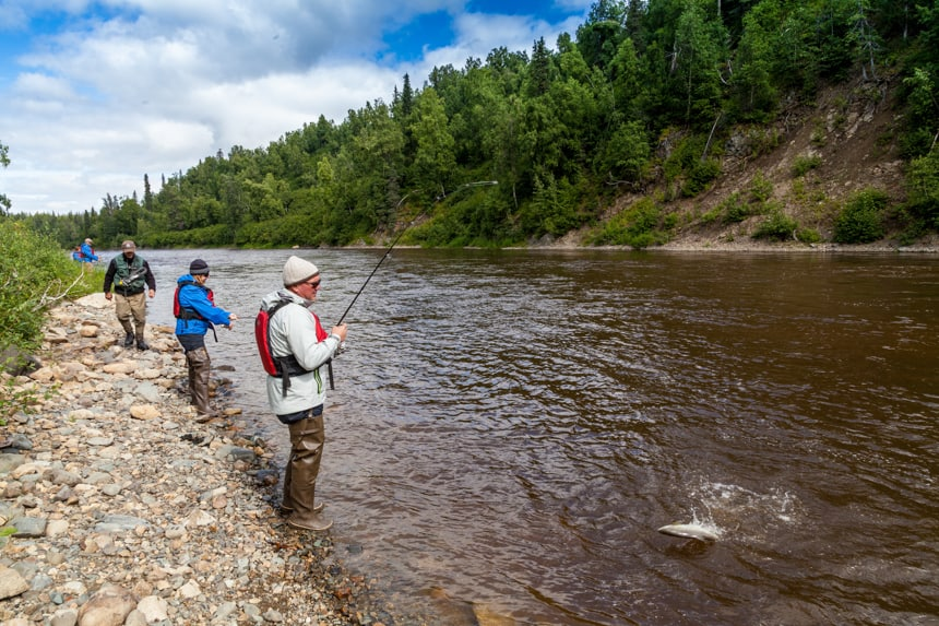 three travelers stand along the banks of a river in Alaska fishing poles in hand, one has a fish on the end of the line, you can see it splash out of the river water. Along the banks are a short hillside of green trees.