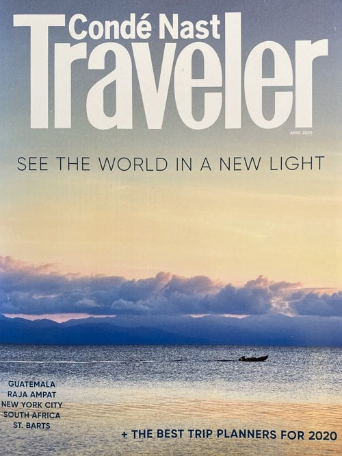 Cover of the April 2020 issue of Conde Nast Traveler magazine. A Peach sunset with purple clouds reflect on a body of water with a small man powered boat paddling.