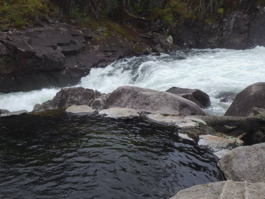 Baranof Warm Spring, a circular pool of water surrounded by rocks, sits against a rushing river, a group of cruise passengers visited on their Alaska small ship cruis