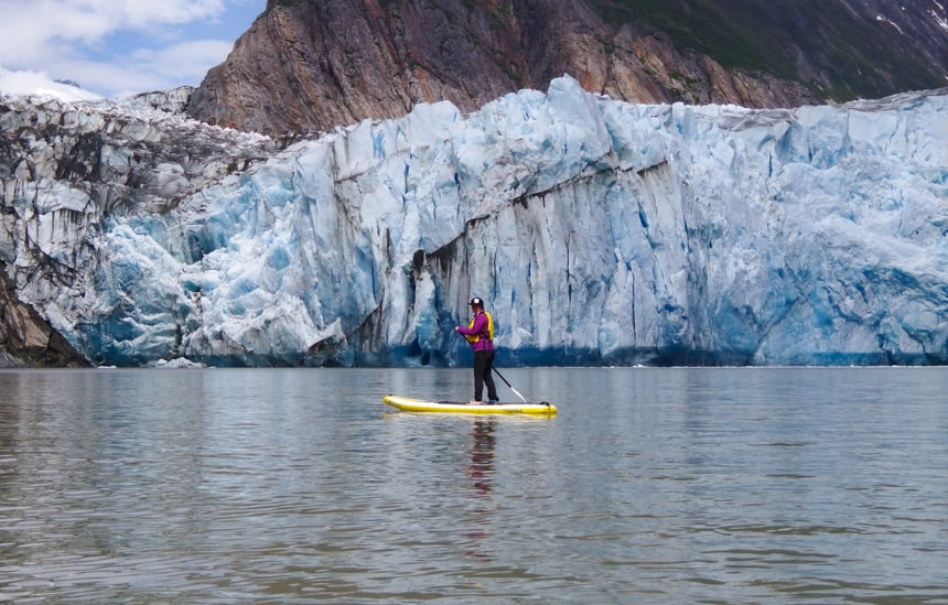a female traveler wearing a yellow life jacket and pink long sleeve sweater, paddles on a stand up paddle board infront of a Glacier on a small ship cruise in Alaska.
