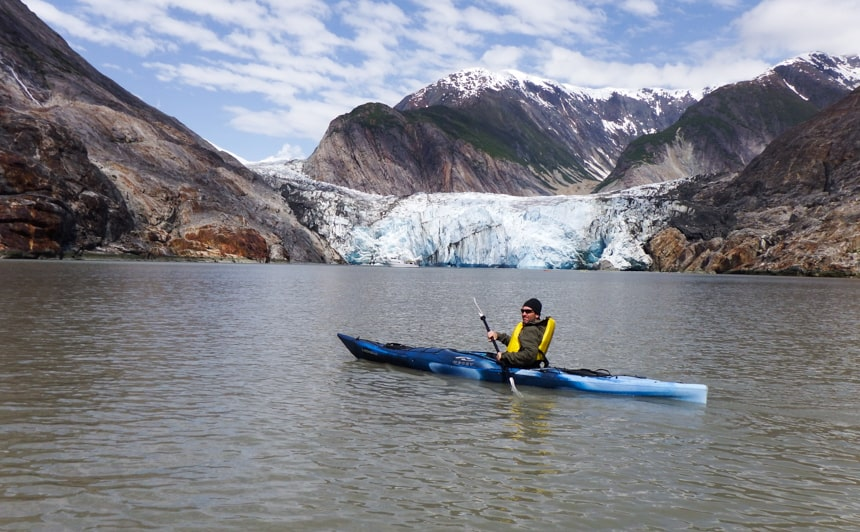 A single kayaker wearing a yellow life jacket paddles a blue kayak in front of a glacier on a blue sky day in Alaska on the islands whales and glaciers cruise.