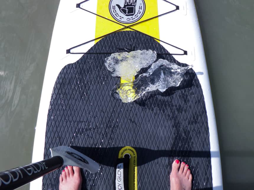 Shot from above, you see someones feet standing ontop of a white and black paddle board that is floating in water, two crystal pieces of ice are ontop with the end of a paddle.