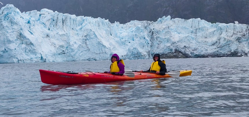 two happy guests paddle a red tandem kayak behind them is a jagged teal and white glacier, an activity done on Islands whales and glacier small ship cruise