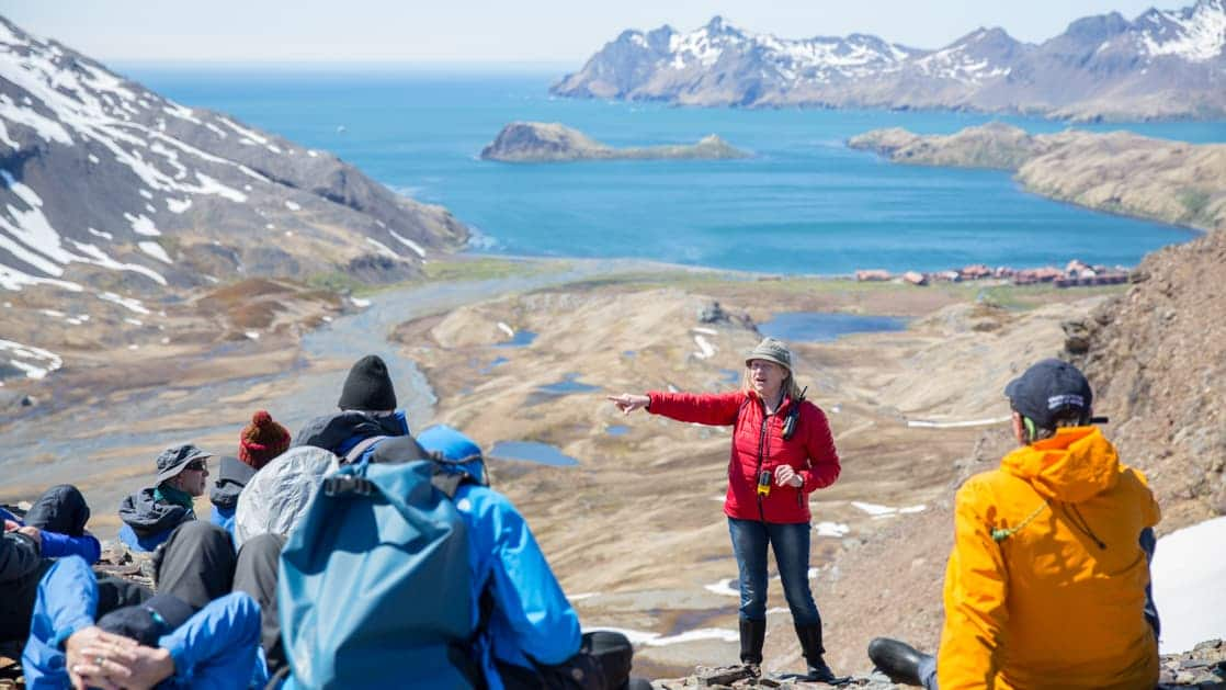 A woman in a red jacket stands & points in front of a group sitting on top of a tan mountain range during the South Georgia Antarctic Odyssey Cruise.
