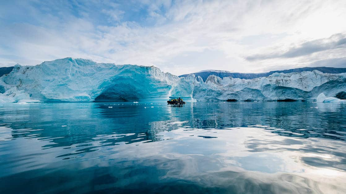 A Zodiac with polar travelers cruises past blue icebergs in a calm bay on a partly sunny day during the South Georgia Antarctic Odyssey Cruise.