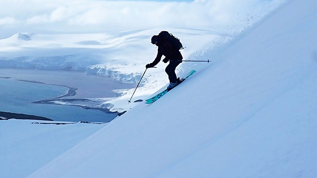 A backcountry skiier makes turns down a steep slope in Antarctica, on a cloudy day.