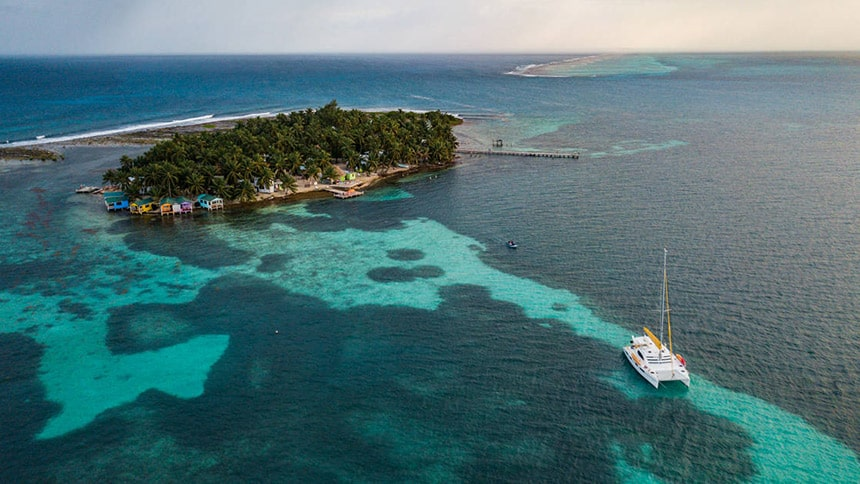 Seen from above a small white Belize catamaran floats in crystal clear ocean water in front of a tiny palm tree covered island, a popular option for private charter.