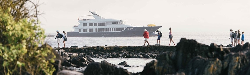 A group of travelers walk along a rocky trail in front of the ocean, behind them on the horizon floats the Galapagos luxury yacht the Origin.