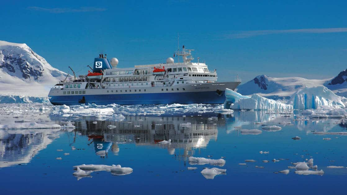 Blue & white Seaventure small expedition ship in Antarctica on a sunny day with calm seas & snowcapped mountains behind.