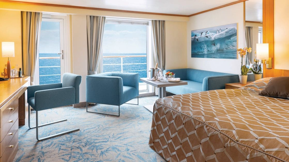 Owner's Suite aboard Seaventure Antarctica small ship, with queen bed covered in brown bedspread, sitting area with couch & chairs, & large balcony.