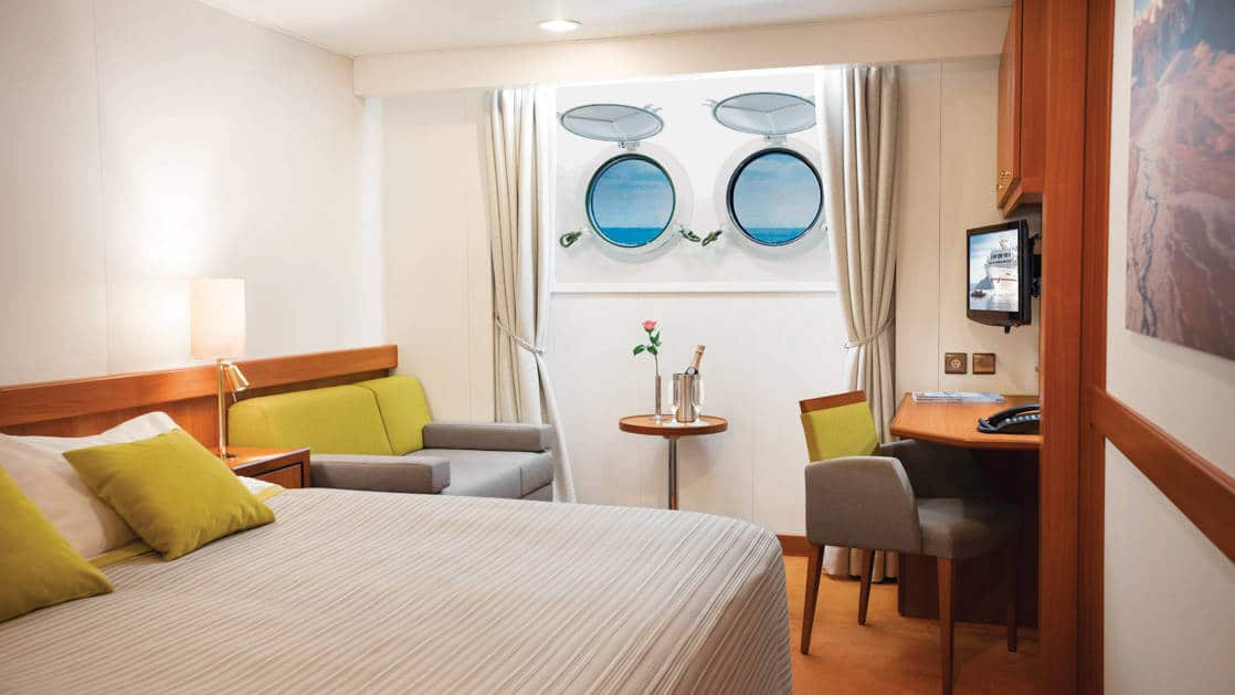 Porthole Stateroom on Seaventure expedition ship, with queen bed, desk, chair, TV & 2 portholes.