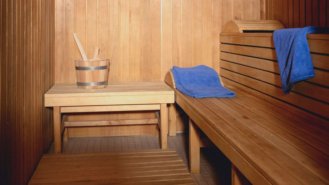 Wooden sauna with water pail, headrests & blue towels aboard all-inclusive ship Seaventure.