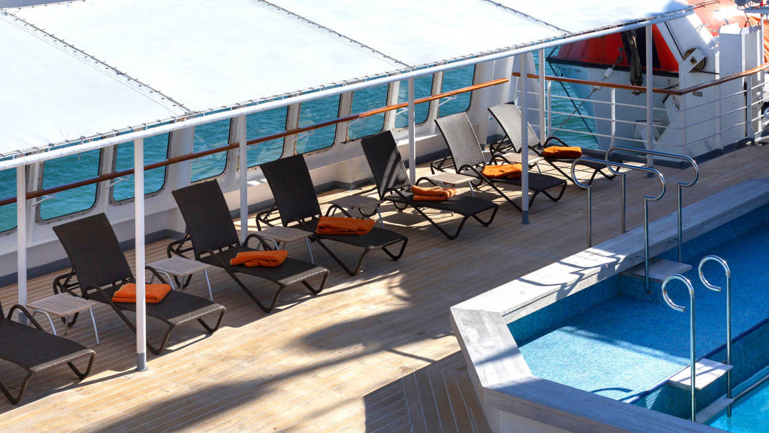 Heated saltwater pool with covered, wind-protected chaise loungers on top deck of M/S Seaventure ship.