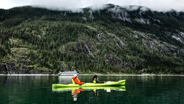 Two guests enjoy a kayaking activity inside the waters of Endicott Arm, an experience to remember after combining their Alaska land tour with a cruise.
