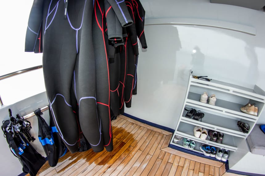 The snorkel station aboard Camila Galapagos trimaran, long black wet suits hang to dry with bags of masks, fins and snorkels, next to them a 6 row shelf with shoes