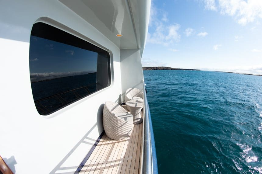 The private balcony of cabin 4 aboard the Camila Galapagos trimaran - teo chairs and a small round coffee table look out over the ocean